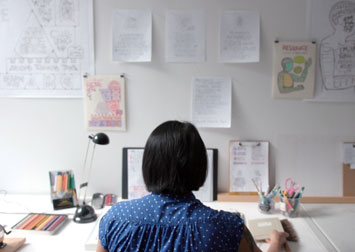 photo of Christine sitting at a desk with drawings on the wall and lots of pencils and art materials on the table