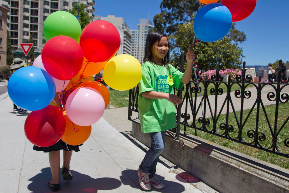 two kids with lots of balloons