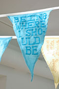 a close-up of a pennant flag sewn of aqua linen with the text 'being where i should be' spelled out in ribbon