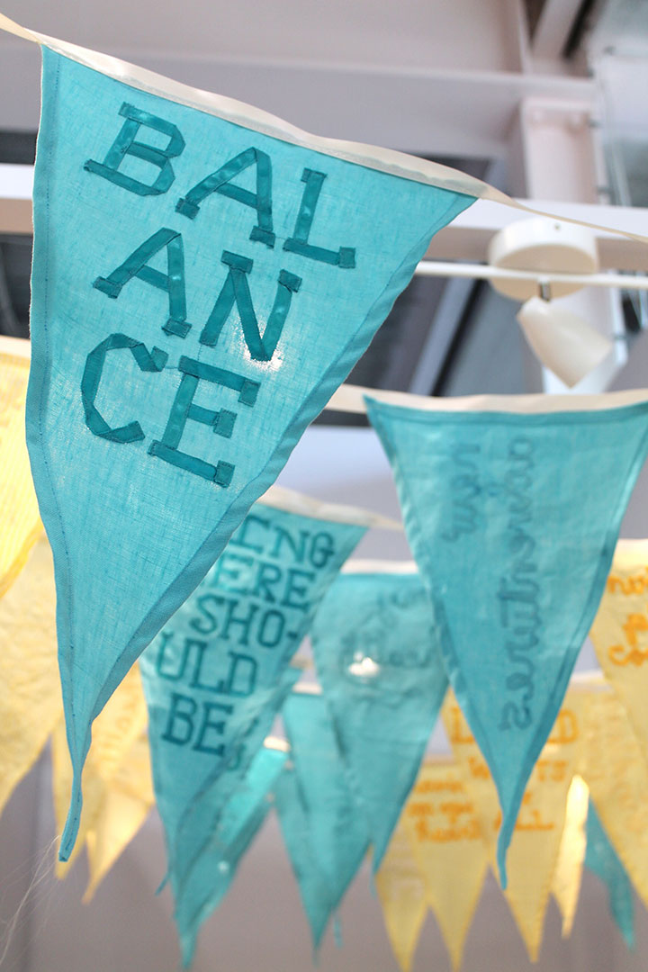 a close-up of a pennant flag sewn of aqua linen with the text 'balance' spelled out in ribbon.