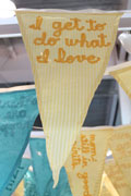 close-up of a pennant flag sewn from yellow seersucker fabric with the text 'i get to do what i want' sewn on in sunflower yellow ribbon