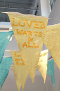 close-up of a pennant flag sewn from yellow seersucker fabric with the text 'loved, warts and all' sewn on in sunflower yellow ribbon