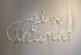 detail of text sewn from pennant ribbon, spelling out 'give thanks' in cream ribbon in cursive