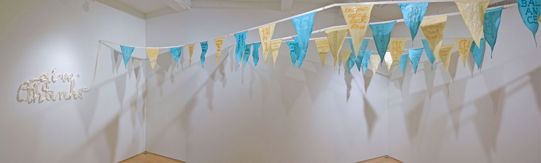 2011, site-specific installation of 39 pennant flags: satin ribbon, linen, gratitude statements, installed dimensions site-variable, hoist ribbon ~73.5 ft long.