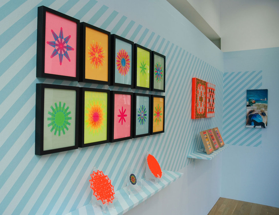 Installation view: from left to right: Flag Snowflakes and Plates series, Hankies, 2009–10, Edition of two embellished handkerchieves: fluorescent handkerchiefs, place mats, thread, wood, 18 x 18 x 2 inches / 46 x 46 x 5 cm each; This Too Shall Pass, 2010, Edition of three papercut collages: paper, calendars, adhesive, customized rabets and frame, painted shelf, 48 x 10 x 12 inches / 1.2 m x 25 cm x 30 cm