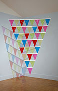 a large triangular, flat sculpture made of smaller triangular pennant flags of transparent multi colored vinyl.