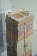 a shelf displaying a stack of cards bounded by clear plexi tubes. each card has a row of paper strips. Strips are embedded with seeds.