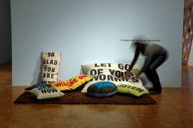 a blurry figure leaning over a carpeted area populated with pillows bearing messages like 'let go of your worries', 'so glad you are here.' it's in front of a pale blue wall with the vinyl text instructions, 'it begins by resting on the pillows.'