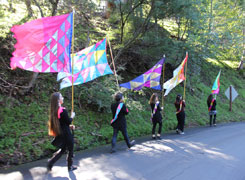 Four flagbearers walk down a hillside road in the woods carrying colorful flags on flagpoles. The flagbearers are also wearing sashes that match the flag they are carrying.