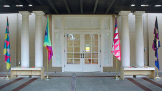 Four flags on gold flagpoles with gold bases. Each pair of flags frames a bench with colored stripes on the top. Everything is on a columned veranda of a gallery with wooden-framed glass doors in the center.