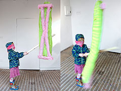 a young girl in a raincoat swings at the ironing board piñata, two images showing the motion