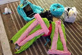 A pile of broken piñatas on a concrete floor