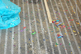 a photo of part of piñata and confetti on the ground
