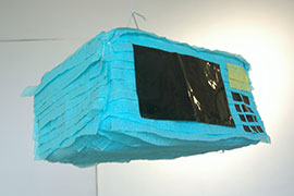 a piñata of a microave, made of blue streamers and black vinyl