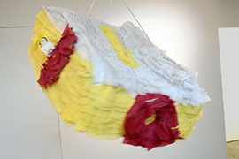 a photo of a piñata modeled after a dewalt travel-sized table saw made of yellow streamers for the sides, white streamers for the top, and red streamers for the knobs and miter gauge