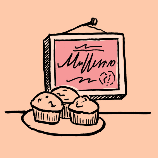 a framed certificate hanging on a wall abovea dish of muffins