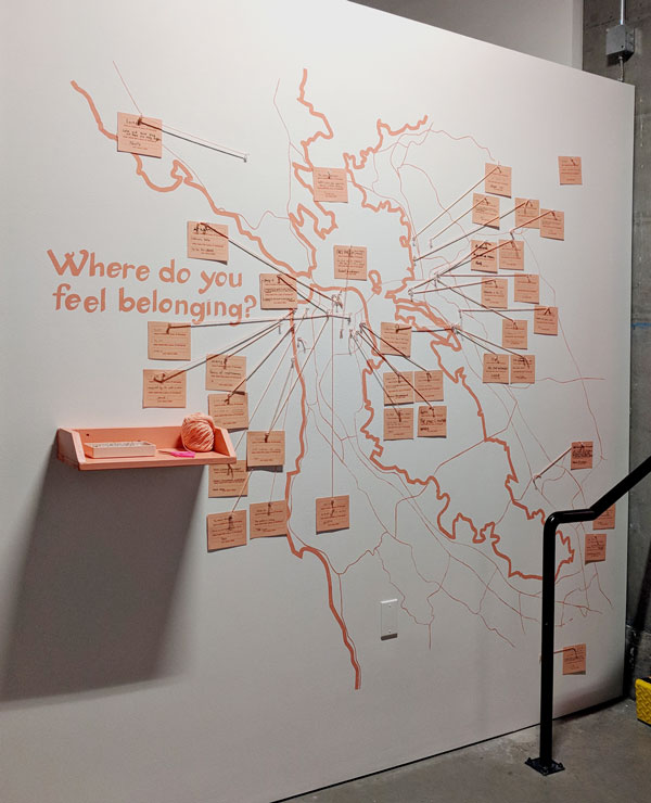 where do you feel belonging in the bay area. photo of a wall in a gallery. there's a map of the bay area painted on the wall, with a shelf with pins. there are cards marking specific places in the bay area.