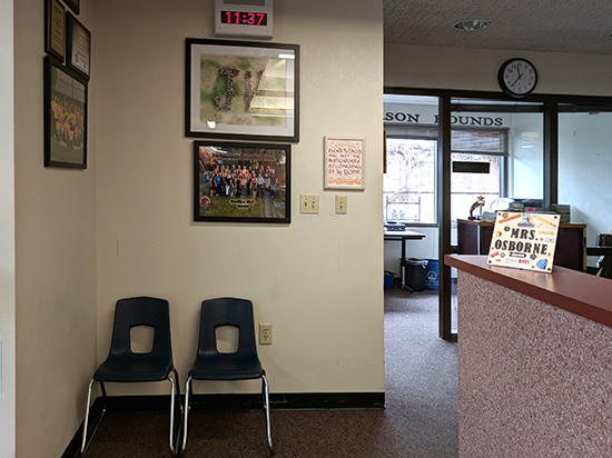 The certificate installed on a wall with a group photos. There are two child-size chairs in front of the wall. To the right is a counter where a handmade sign reads Mrs. Osborne. In the background is the principal's office.