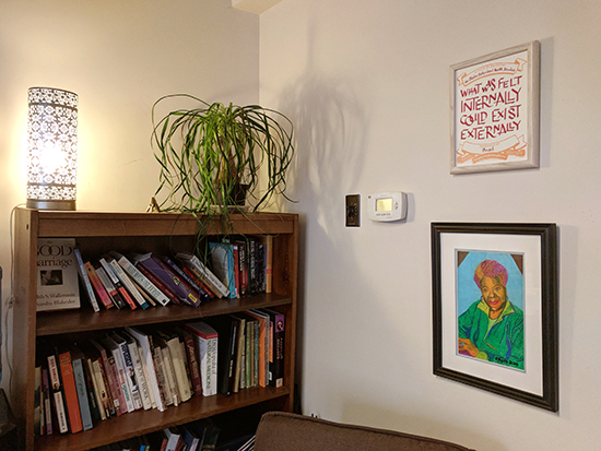 The certificate installed above a drawing of Maya Angelou, which is above a comfy chair. It's to the right of a softy-lit lamp  and a houseplant on top of a bookshelf.