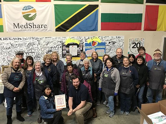 A group of about two dozen volunteers wearing aprons. They are in a warehouse. Behind them is a wall covered in different countries' flags. In front of them are the artist holding the certificate and Eric Talbert.