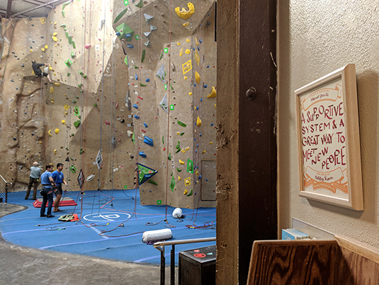 Certificate hanging on a wall on the right of the image. In the distance is an indoor rock climbing gym. A few climbers are on the ground, while one climber is on the wall.