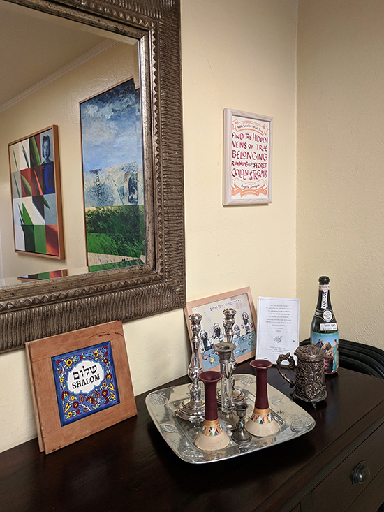 certificate next to a mirror with paintings in the reflection. Below are artworks and  Judaica.