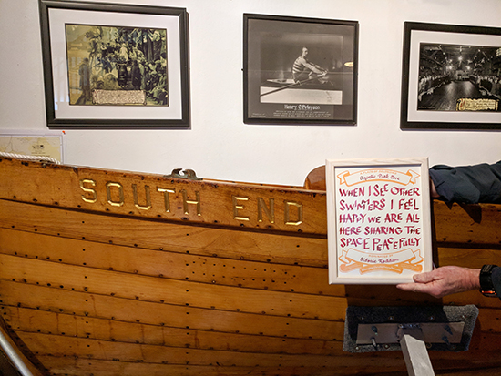 Hand holding a certificate in front of a boat with the words South End. Behind the boat are black and white photos of rowers on the wall.