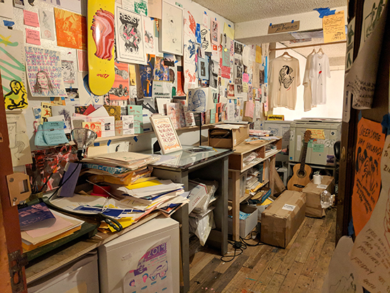 Certificate in a printing studio with prints, skateboard decks, and posters all over the walls.