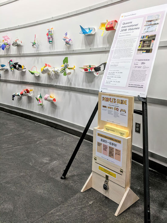 a wood stand with forms and a submission box beneath a sign in front of children's art