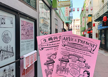 photo of two comic books, one in english, one in chinese, about art, culture and belonging in Chinatown, held up in an alleyway with festive lanterns