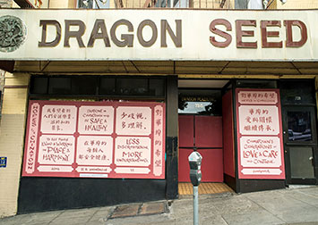 photo of artwork with text in chinese and english in pink and red on a boarded up storefront in Chinatown with masked passersby