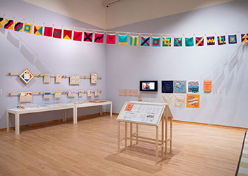 installation view of an exhibit, with color flags strung overhead