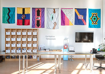 a photo of an installation of colorful flags in an art studio room